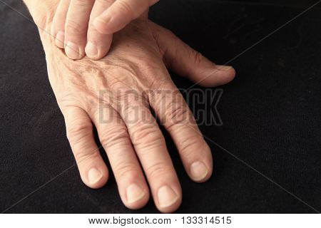 Senior man with pain on the back of his hand copy space included