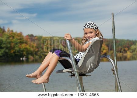 joyful pretty little girl sitting and relaxing above the water in the life guard chair against natural autumn background on sunny warm beautiful day