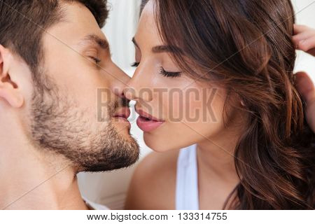 Close-up portrait of two lovers couple kissing over white background