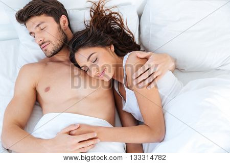 Lovely beautiful young couple sleeping on their bed at home