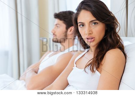 Upset woman sitting in the bed with man on the back at home