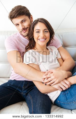 Close-up portrait of a beautiful young smiling couple sitting on sofa isolated on white background