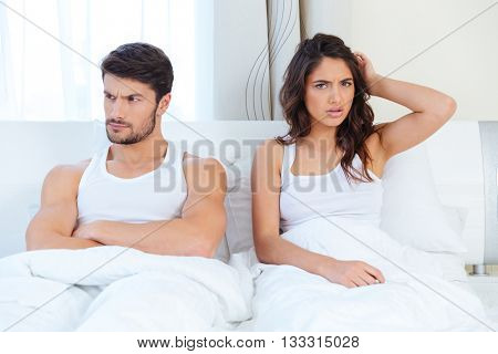 Unhappy separate couple lying in a bed at home