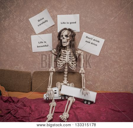 Skeleton in a wig sitting on the bed with truck and trailer model on his legs, leaning against the wall with various messages about safety driving behavior and consequences on the road