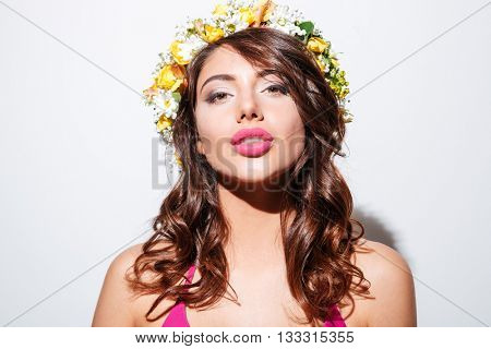 Close-up portrait of a beautiful attractive girl wearing flower diadem isolated on the white background