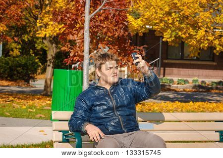 young adolescent sitting on the bench in autumn sunny warm park and making self photograph on his cellphone