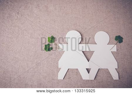 paper dolls holding hands with green leaves