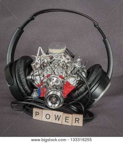 Old dusty, miniature detailed ,shiny truck engine standing between a black headphones with message word in front