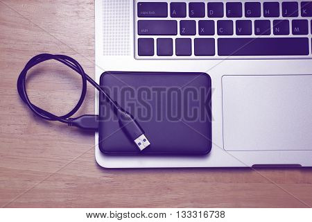 External hard disk and laptop computer on wood background.