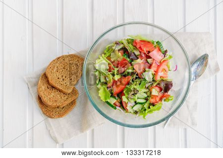taste of vegetarian summer concept salad of lettuce leaf tomato cucumber onion oregano with olive oil and lemon juice on white wooden background with copyspace