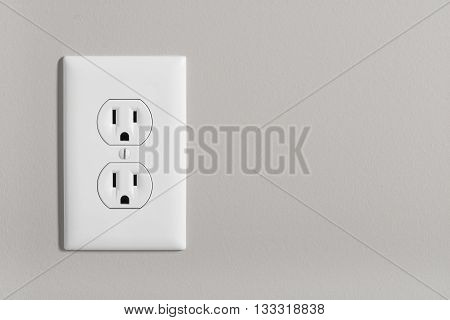 A white home electrical outlet on a light grey wall.