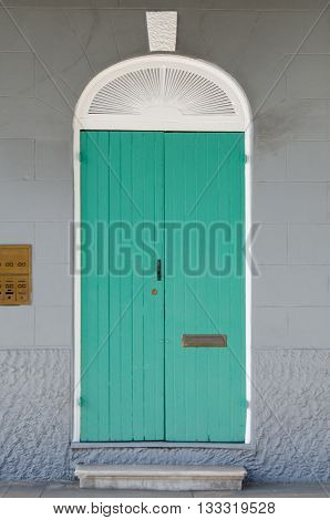 A brightly painted aqua door against a subtle gray wall