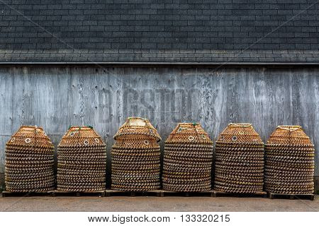Crab pots for the commercial crab fishery stacked up on a wharf in rural Prince Edward Island, Canada.