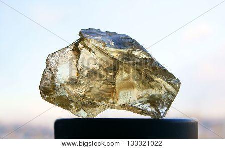 Transparent rough yellow quartz citrine on black stand in natural light