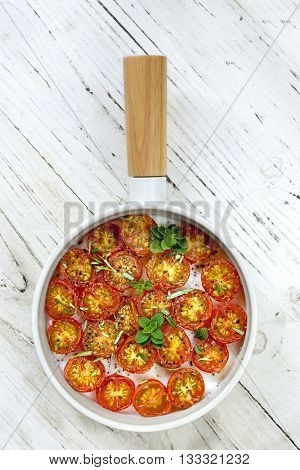 Roasted cherry tomatoes in white pan over rustic timber.  Top view.