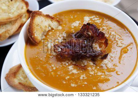 Butternut pumpkin soup, with crispy pancetta, parmesan and garlic bread.