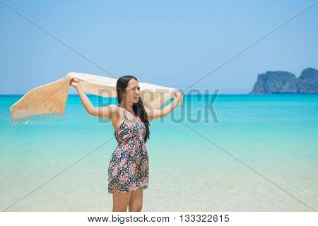 A woman on vacation stands profile on a tropical paradise beach and holds a sarong in the wind, travel destinations and freedom.