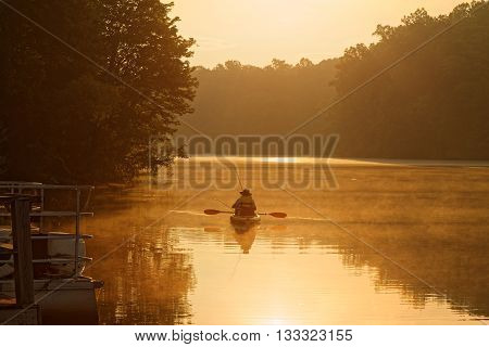 A fisherman on a kayak at sunrise.