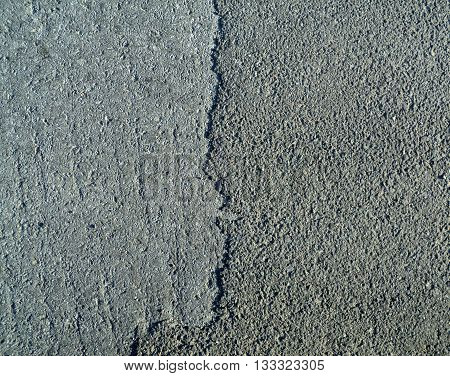 Grey asphalt ground surface texture with cracking, top view of a worn road, photo image.