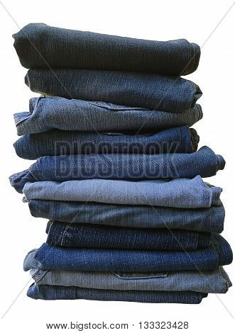 Large stack of woman's blue jeans folded in a neat pile and isolated on a white background, denim clothing photo image.