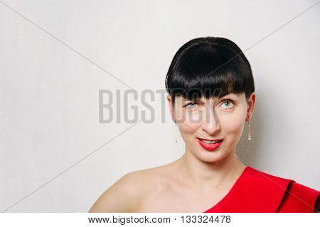 Beautiful young model woman in red dress posing over white background
