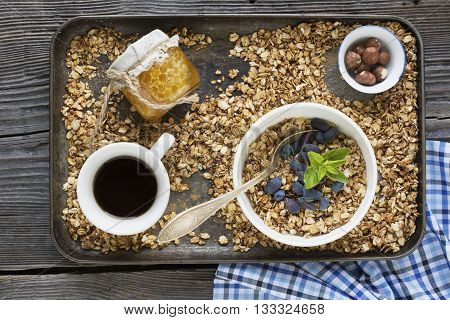 Healthy breakfast. Ready-baked granola with honey on a tray for a healthy healthy breakfast with berries, honey, nuts and a cup of coffee.