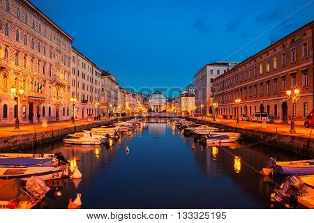 Trieste, Italy. Church of St. Antonio Thaumaturgo with Canal Grand in the evening. Sunset sky with boats and illuminated buildings