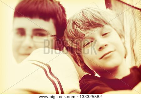 Blurred sepia toned tilt shift lens image of two boys.  Shallow focus down the middle, in camera effect.