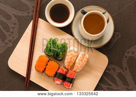 Sushi Set With Chop Sticks And Soy Sauce Served On Wooden Slate - Sushi Is A Food Originating In Jap