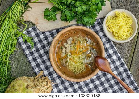 Top View on a Chicken Broth with Carrots Celery Parsley and Noodle in Wooden Bowl with Spoon on a Old Wooden Table