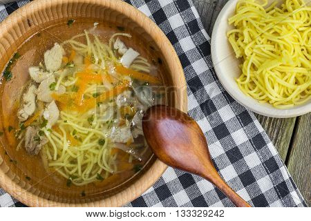 Detailed Top View on a Chicken Broth with Carrots Celery Parsley and Noodle in Wooden Bowl with Spoon on a Old Wooden Table