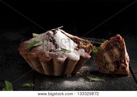 Chocolate cake with cherry (sprinkled with powdered sugar and mint leaves). Piece of cake. Low key photo