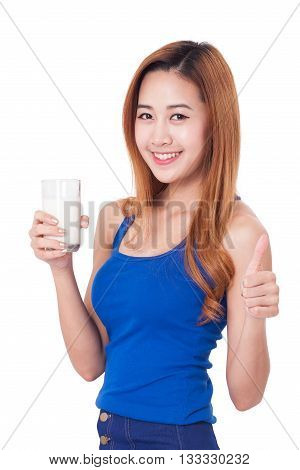 Portrait of happy young woman holding glass of milk and showing thump up.