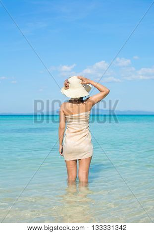 Asian Woman Wearing Sarong And Summer Hat At Beach.