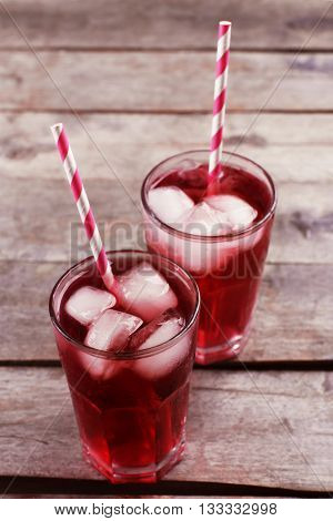 Glasses of red soda water with ice blocks on wooden table
