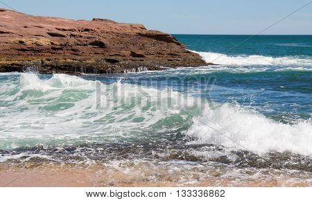 Turquoise Indian Ocean waves rushing cove and sandstone rock formations in Pot Alley under clear blue skies in Kalbarri, Western Australia.