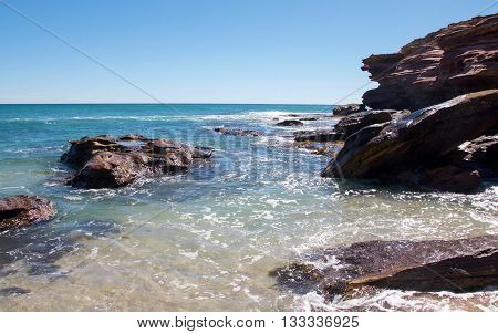 Turquoise Indian Ocean seascape with natural sandstone rock formations at the secluded cove at Pot Alley under clear blue skies in Kalbarri, Western Australia.