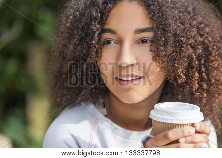 Beautiful happy mixed race African American girl teenager female young woman smiling drinking takeaway coffee outside