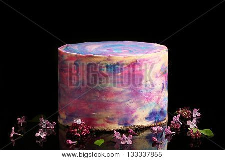 Colorful frosted cake on black background