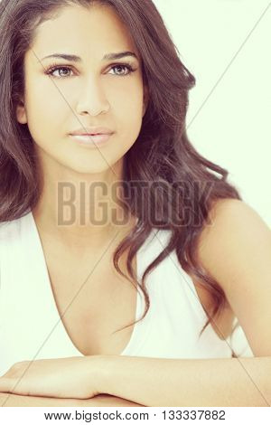 Studio portrait of a beautiful young Latina Hispanic young woman or girl looking thoughtful