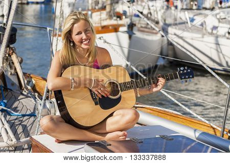 A beautiful blond young woman sitting on the deck of sail boat or yacht in natural golden summer sunshine having fun playing her guitar