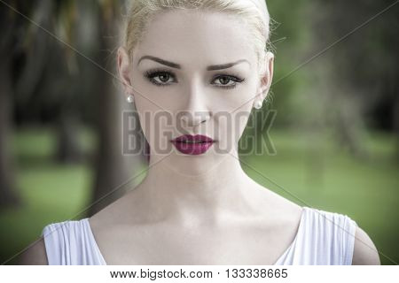 Beautiful young blond woman with pink lipstick wearing a white dress looking directly into the camera
