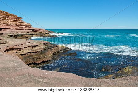 Indian Ocean seascape, sandstone cliffs and inlet on a clear day in Pot Alley, Kalbarri, Western Australia.