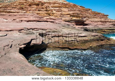Pot Alley's natural sandstone recess with Indian Ocean waters and sandstone cliffs under clear blue skies in Kalbarri, Western Australia.