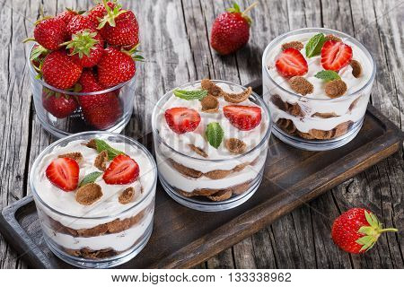homemade yogurt in cups with whole grain cereals strawberry decorated with mint leaves on a dark brown wooden tray on a rustic table close-up studio lights top view