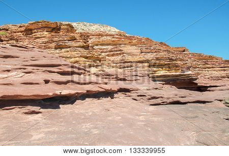 Layered landscape at Pot Alley gorge with unique red sandstone formations under clear blue skies in Kalbarri, Western Australia.