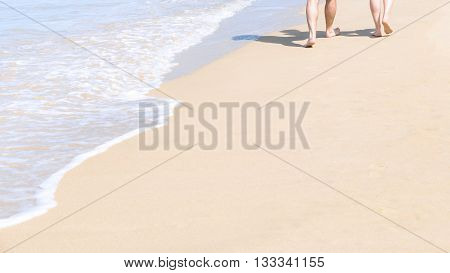 Couples walking on tropical sandy beach in vacations. Shadow on sand.