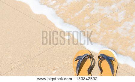 Tropical vacation concept - sandal on a sandy beach