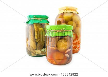 Homemade pickled green and red tomatoes with cucumbers, carrots and onions in glass jar with paper wrapper. Homemade preserves, pickles. Jar of canned marinated tomatoes and cucumbers isolated