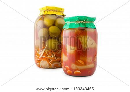 Homemade pickled green tomatoes with zucchini, carrots and onions in glass jar with paper wrapper. Homemade preserves, pickles. Jar of canned green marinated tomatoes and zucchini isolated on white